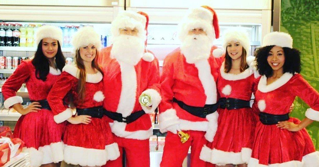 Saxofoon spelende kerstmissen en kerstmannen vermaken personeel Douwe Egberts